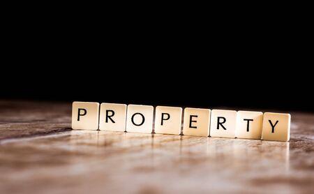 Property word made of tiles on dark wooden background Banco de Imagens