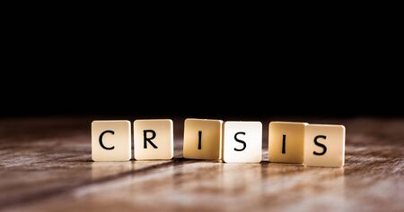 Crisis word made of tiles on dark wooden background