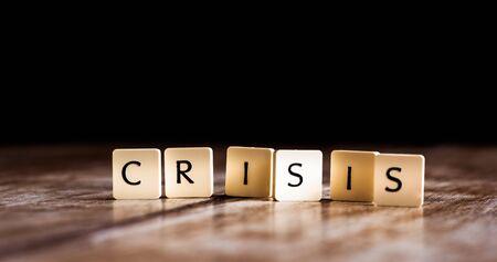 Crisis word made of tiles on dark wooden background Banco de Imagens - 130874045
