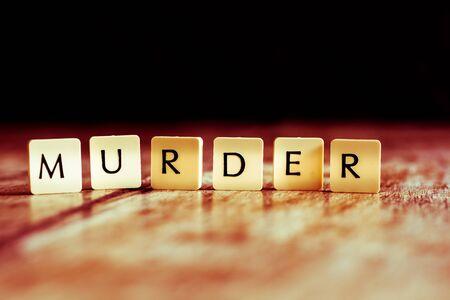 Murder word made of tiles on dark wooden background