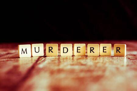 Murderer word made of tiles on dark wooden background Banco de Imagens