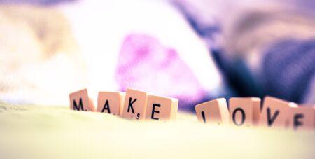 Make love word made of tiles on bed Banco de Imagens