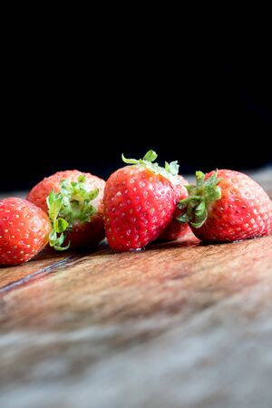Fresh ripe red strawberries isolated on rustic wooden table Banco de Imagens