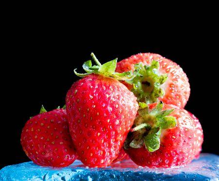 Fresh ripe red strawberries isolated on dark background Banco de Imagens