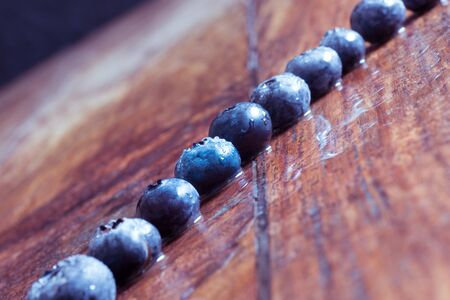 Blueberries lined up on a wooden table Banco de Imagens