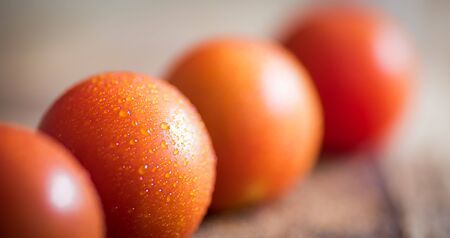 Red ripe tomatoes in line on wooden background Banco de Imagens