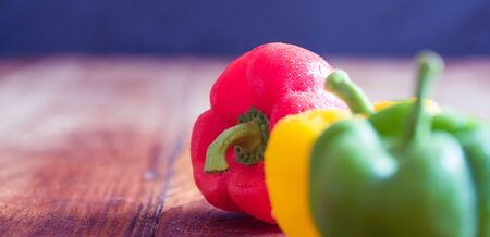 Red, yellow and green pepper on vintage wooden table
