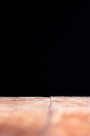 Old wooden floor and black wall background