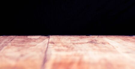 Rustic wooden table and dark background
