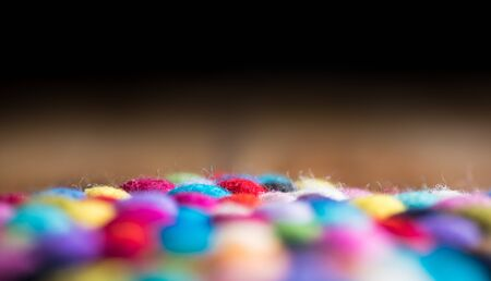 Dark wooden background and colourful fluffy wool balls
