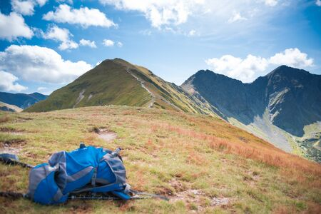 Blue Rucksack and mountain path in the background - trekking equipment, hillwalking gear, mountaineering