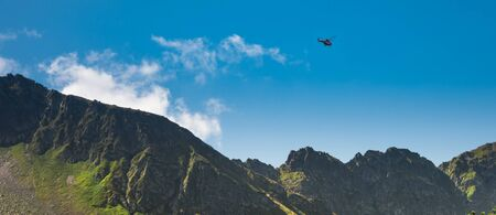 Red helicopter of TOPR (Polish mountain rescue team) during emergency action in Tatra mountains