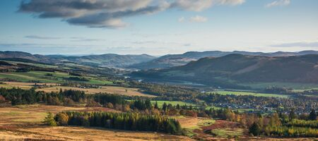 Panoramic view of Pitlochry in Perthshire, Scotland - heather covered hills, meandering river, mountains
