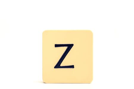 Dark letter Z on a pale yellow square block isolated on white background