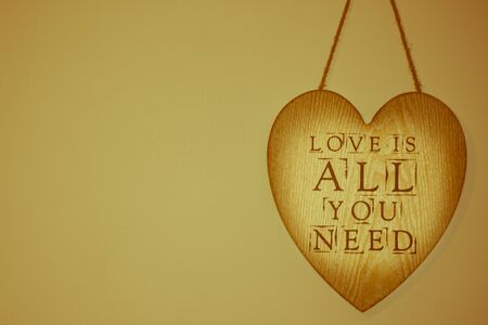 Love is all you need in a wooden heart hanging on a wall