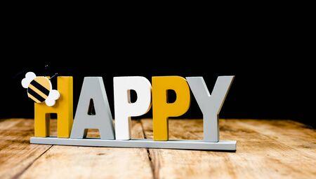 Happy - joyful sign with bee isolated on dark wooden background Stockfoto