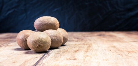 The kiwi fruit on a wooden table and black background Stockfoto