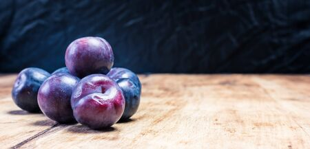 Close-up of ripe home plums on a wooden background in the garden. natural healthy vegan food