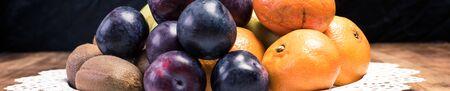 Health diet ingredients - fresh fruit: banana, plum, kiwi and orange