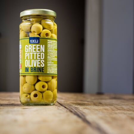 Perth, Scotland - 11 November 2019: Green pitted olives in brine isolated on vintage wooden table Stockfoto