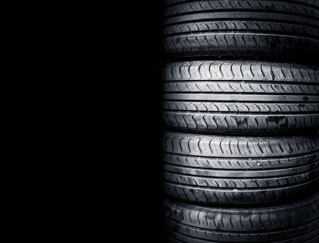 Studio shot of a set of summer car tires isolated on black background. Tire stack background. Stock fotó