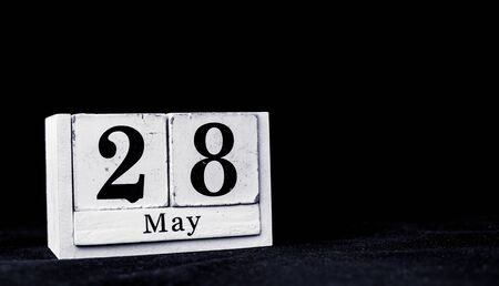 May 28th, Twenty-eighth of May, Day 28 of month May - vintage wooden white calendar blocks on black background with empty space for text