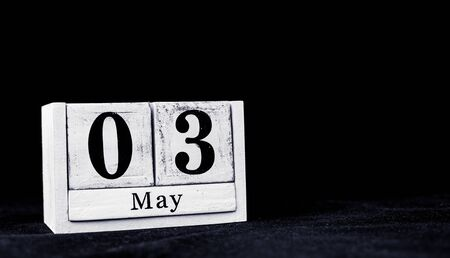 May 3rd, Third of May, Day 3 of month May - vintage wooden white calendar blocks on black background with empty space for text