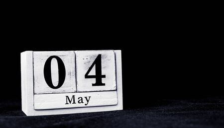 May 4th, Fourth of May, Day 4 of month May - vintage wooden white calendar blocks on black background with empty space for text