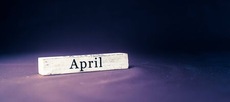 April, name of the month written on vintage white wooden block on purple blue textured background . Banner format.