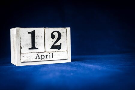 April 12th, Twelfth of April, Day 12 of month April - rustic wooden white calendar blocks on dark blue background with empty space for text