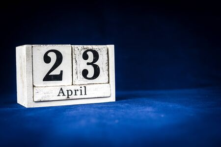 April 23rd, Twenty-third of April, Day 23 of month April - rustic wooden white calendar blocks on dark blue background with empty space for text