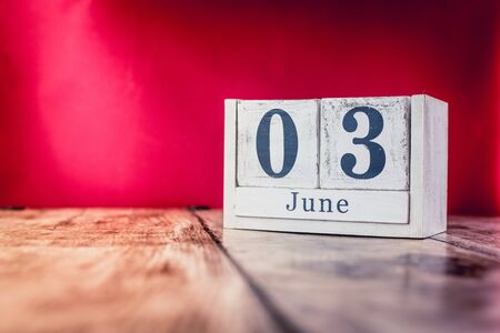 June 3rd. Day 3 of month, calendar on business office table, workplace with vivid maroon red background. Summer time