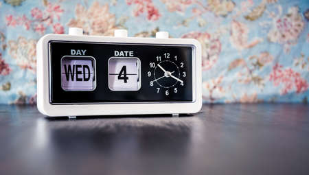 Wednesday 4th of the month - white vintage alarm clock with set date and time