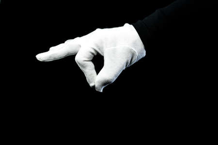 A hand wearing white glove on black background