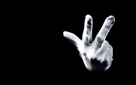 Number three 3 - a male hand wearing white glove isolated on black background. Hand gestures