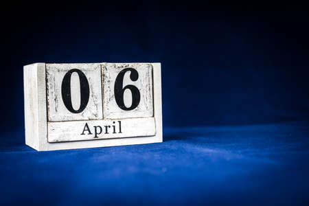 April 6th, Sixth of April, Day 6 of month April - rustic wooden white calendar blocks on dark blue background with empty space for text