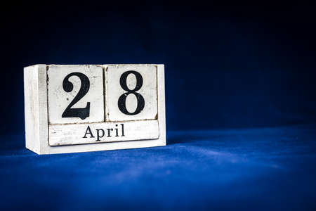 April 28th, Twenty-eighth of April, Day 28 of month April - rustic wooden white calendar blocks on dark blue background with empty space for text