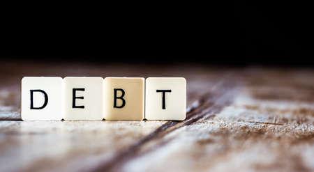 Debt word made of tiles on dark wooden background