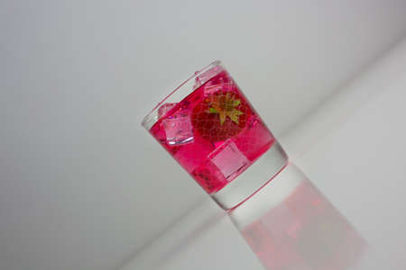 Strawberry juice extract poured into glass of water on white background