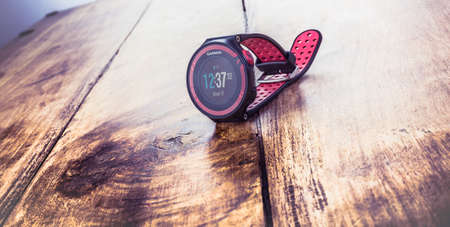 Alloa, Scotland - 17 July 2019: GARMIN FORERUNNER Multisport Watch isolated on wooden background