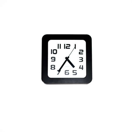 Wall clock - square black wall clock on a white wall