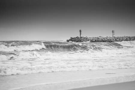 Lighthouse and storm at sea - crashing waves, cloudy overcast sky Stockfoto