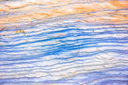 Blue, green, orange rock layers - a colorful formations of sedimentary rocks stacked over the hundreds of years. Abstract background with fascinating texture for graphic design. Stock Photo