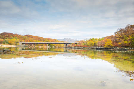 The bridge carrying the A830 road over the River Morar, near Morar, Highlands of Scotland - autumn scenery with orange leaves and trees reflected in water Фото со стока