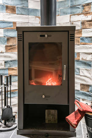 Modern wood burning stove with accessories and red gloves next to it. Wood burning stove with orange yellow flames. 版權商用圖片