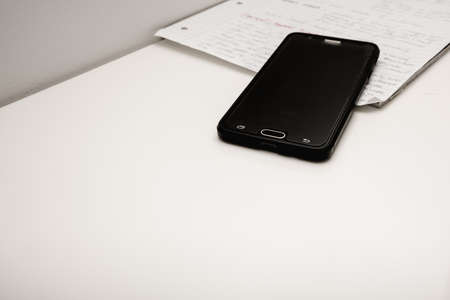 A stack of white sheets of paper, an open notebook, a mobile phone-close-up.