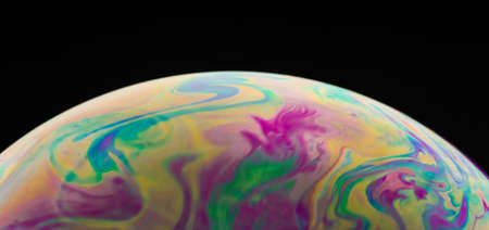 Macro picture of half soap bubble on black ground look like abstract psychedelic color planet in space