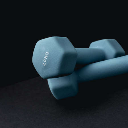 2 kg dumbbells isolated on dark background - home fitness and workout.