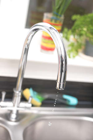 Kitchen tap isolated on bright background. Water saving solutions.