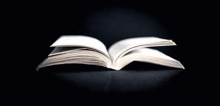 Old vintage open book on black background Standard-Bild